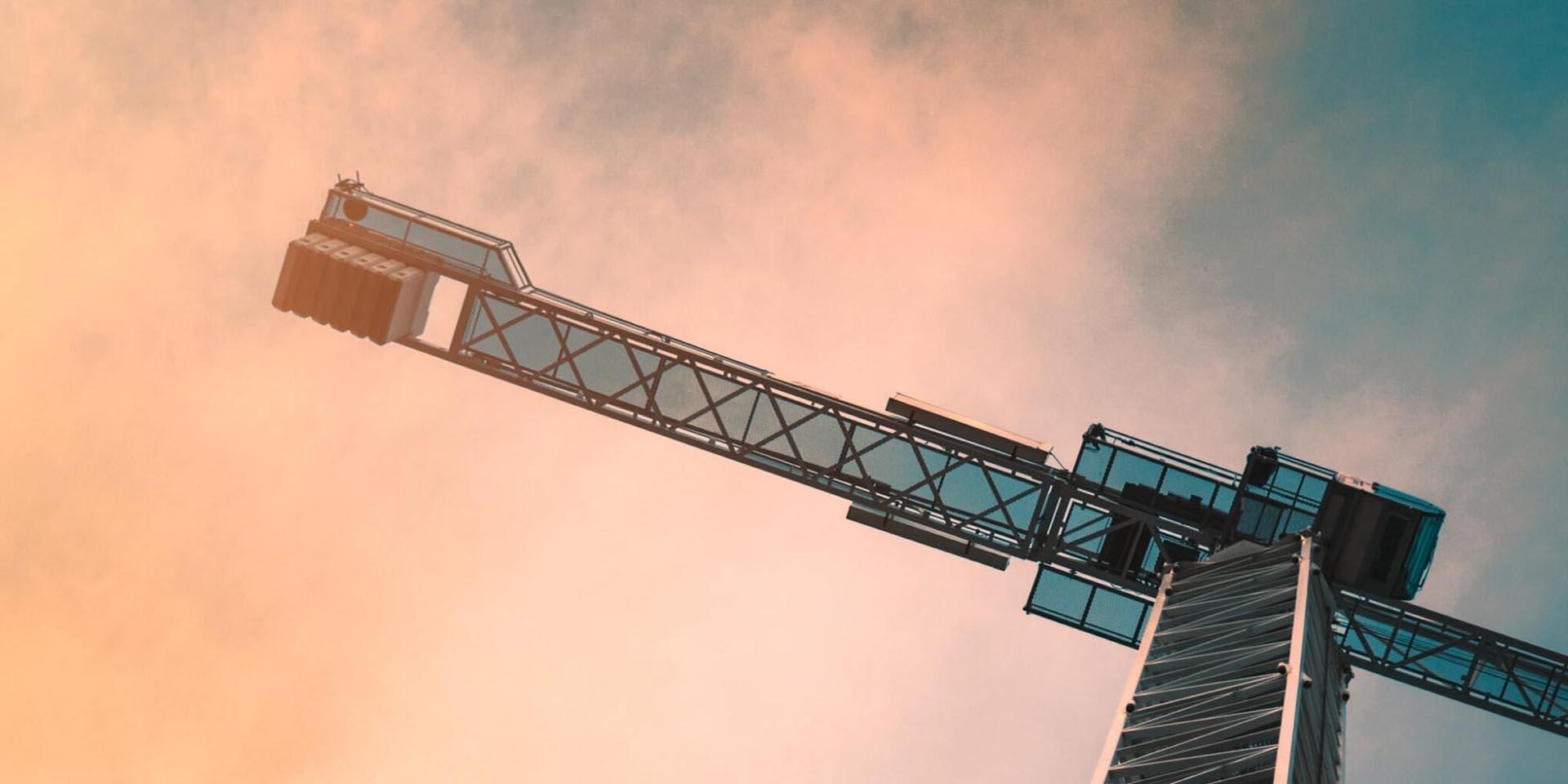 Ein Kran auf einer Baustelle während der Corona Pandemie vor einem wolkig-orangenen Himmel
