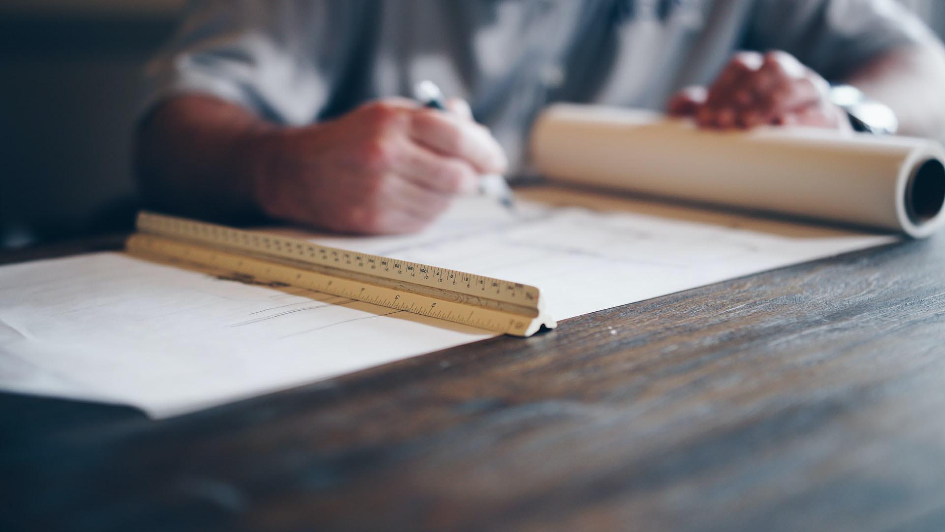 Ein Architekt füllt neben Zeichnungen seinen Bauzeitenplan auf einem Holztisch aus