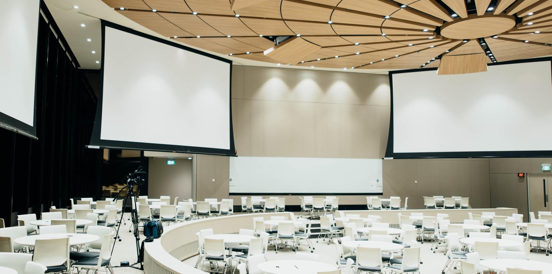 Saal mit 3 großen Bildschirmen und zahlreichen Stühlen, in dem eine Baumesse stattgefunden hat