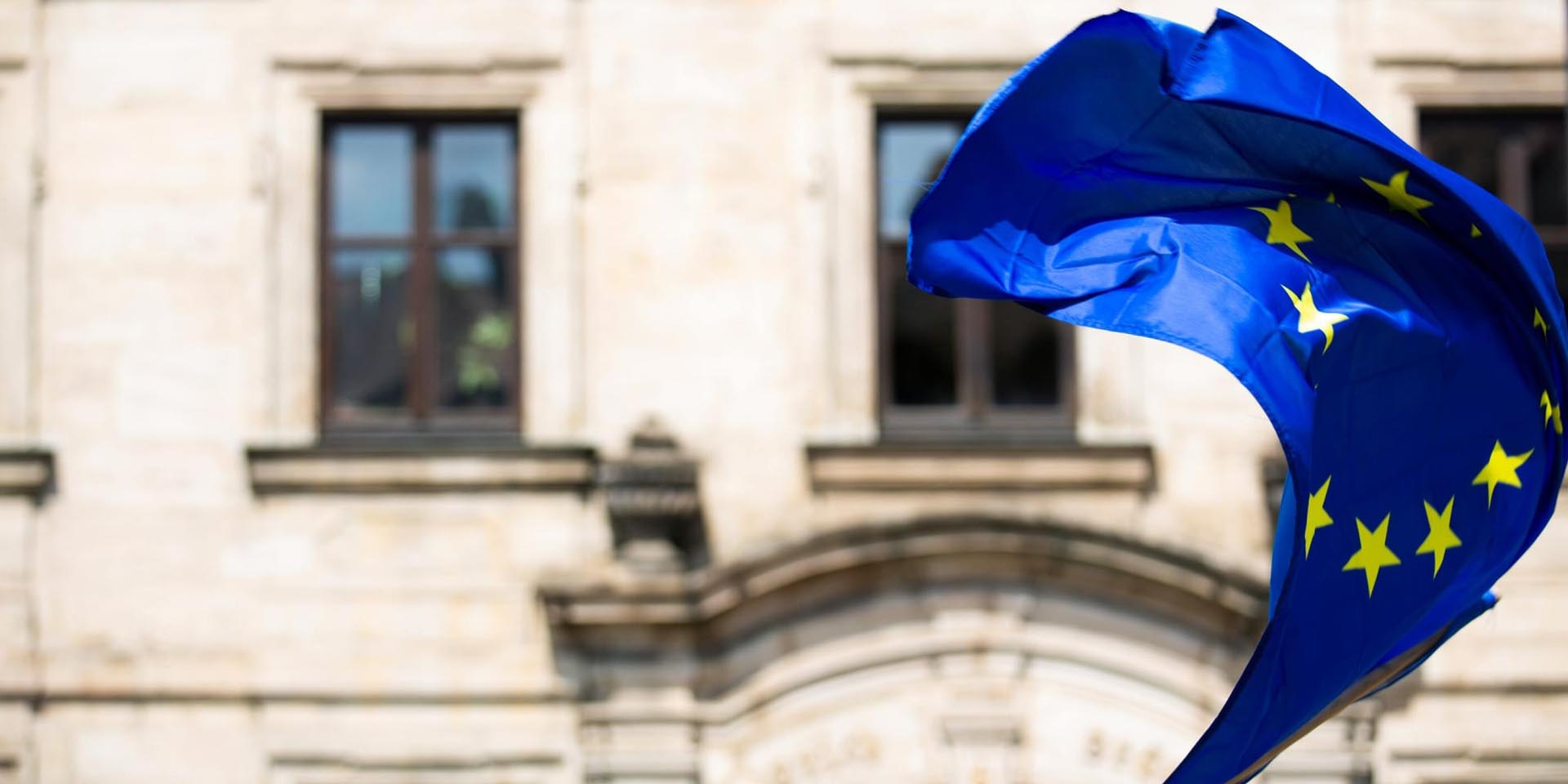 Europäische Flagge weht vor einem historischen Gebäude