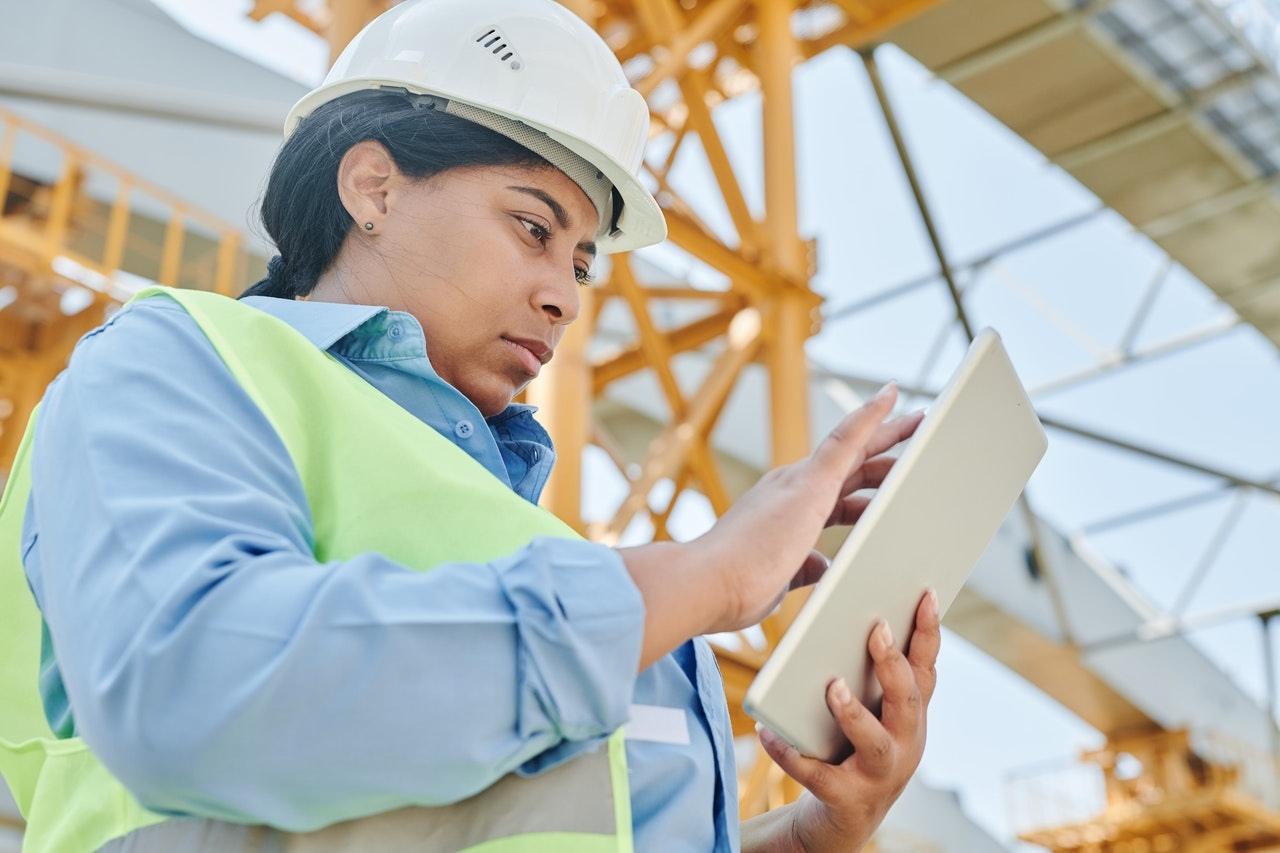 Bauarbeiterin mit Tablet auf der Baustelle