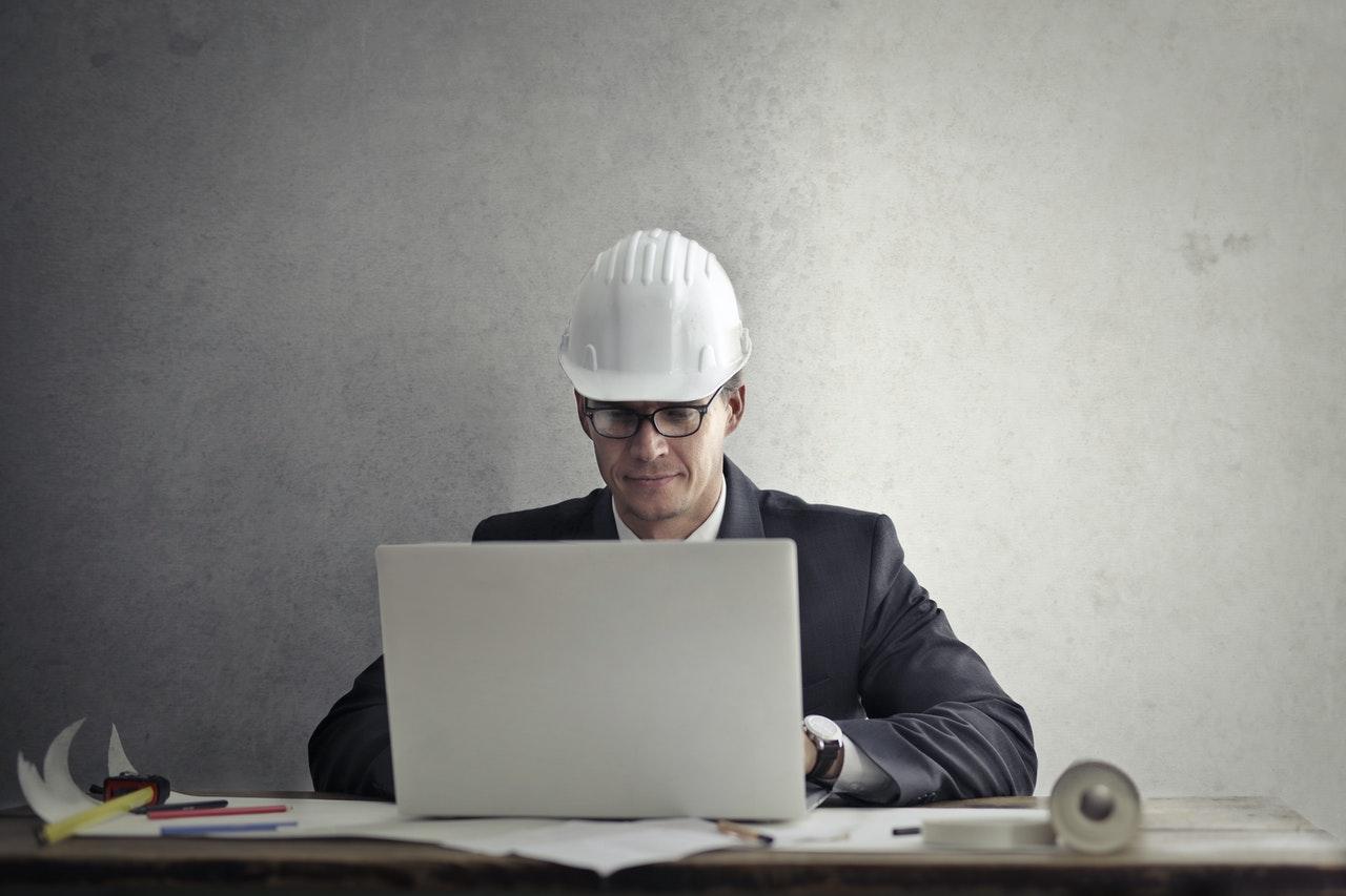 Bauleiter mit Bauhelm am Laptop mit Bausoftware