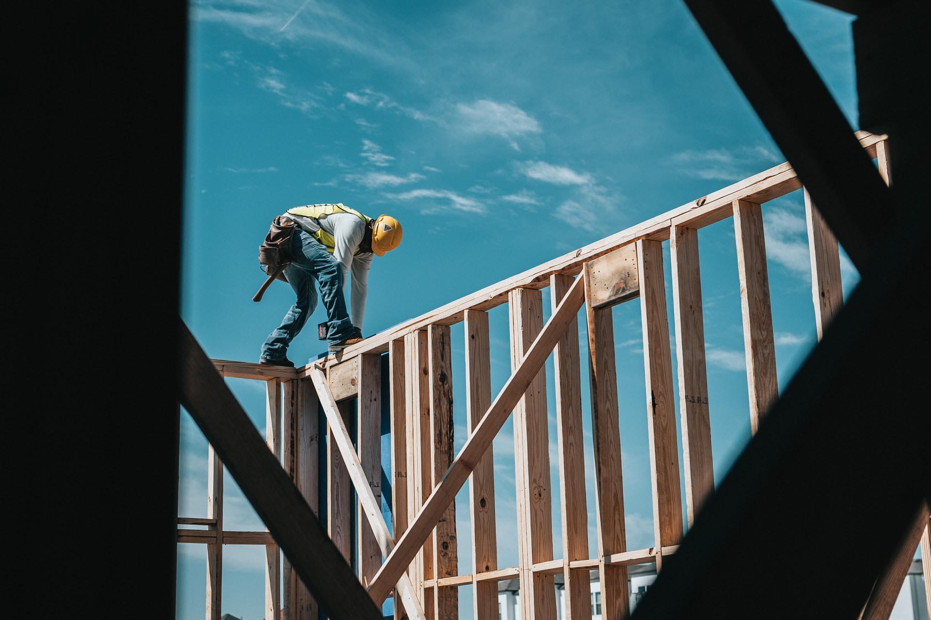 Ein Bauarbeiter steht gebückt auf einem Gerüst aus Holzbalken auf einer Baustelle