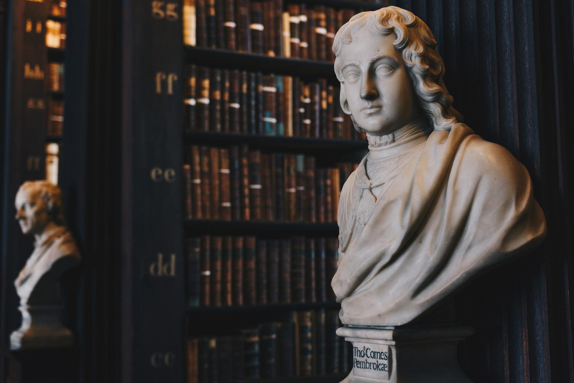 Zwei Büsten stehen in einer alten Bibliothek voller Gesetzbücher