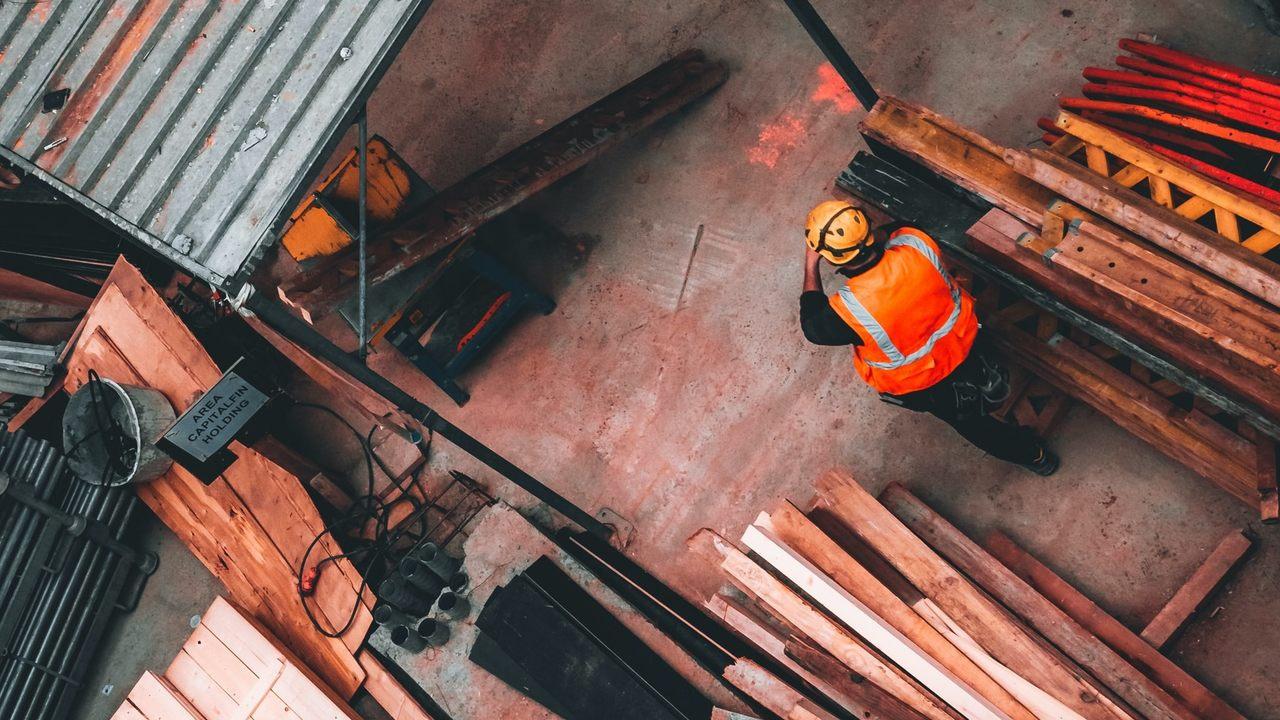 Bauarbeiter auf Baustelle, der sich zwischen Baumaterialien über die steigenden Baukosten ärgert