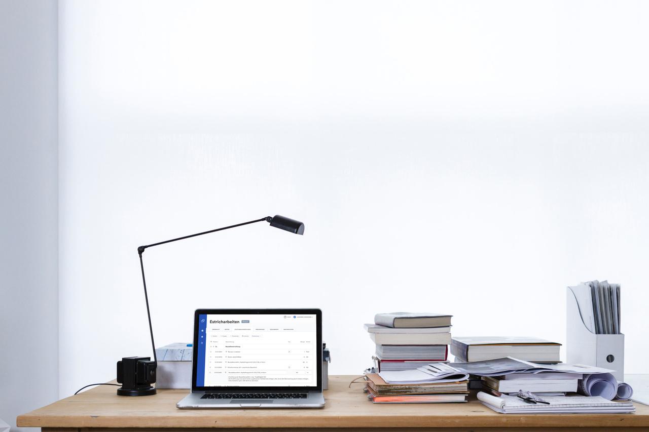 Ein Schreibtisch mit Aktenstapeln, in der Mitte steht ein Laptop, auf dem die Cosuno Software mit Leistungsverzeichnis Editor geöffnet ist